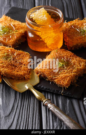 Turkish traditional dessert kadayif with pistachio and honey close-up on the table. Vertical - Stock Photo
