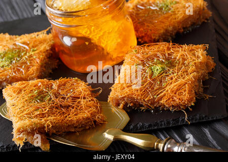 Turkish dessert kunefe with pistachio powder, Kataifi pastry close-up on a table. Horizontal - Stock Photo