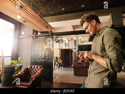 Side view of handsome young man reading text message on his mobile phone and smiling. Creative businessman using - Stock Photo
