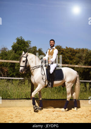 riding man and his stallion in a training of dressage - Stock Photo