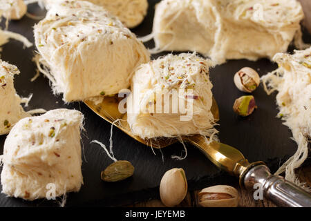 Turkish food: pismaniye with pistachios close-up on the table. Horizontal - Stock Photo