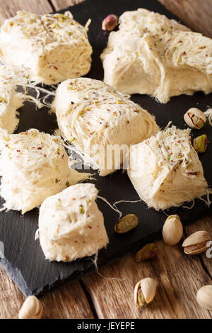 Delicious sweetness of dessert pismaniye with pistachio nuts close-up on the table. vertical - Stock Photo