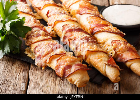 Bread sticks with bacon and cheese close-up and garlic sauce on the table. Horizontal - Stock Photo