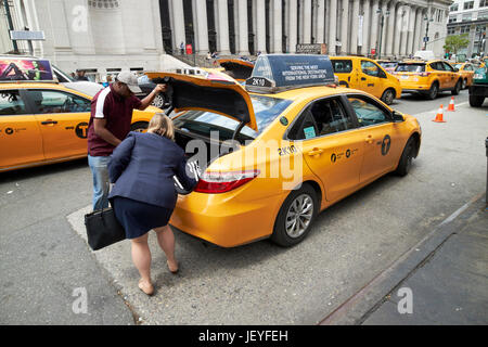 woman putting luggage in the trunk of a yellow cab New York City USA - Stock Photo