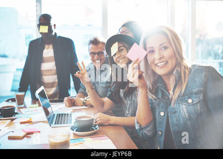 Diverse team of male and female office workers playing with sticky notes at table