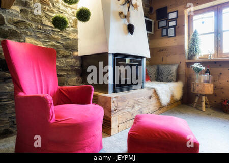 Cozy interior of a rustic chalet with modern fireplace - Stock Photo
