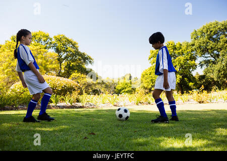 Cute football players playing football - Stock Photo