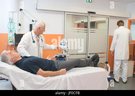 Doctor taking man's pulse - Stock Photo