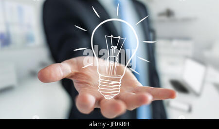 Businessman on blurred background holding a sketch lightbulb - Stock Photo