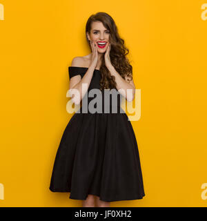 Beautiful young woman in elegant black cocktail dress is holding head in hands, laughing and looking at camera. - Stock Photo