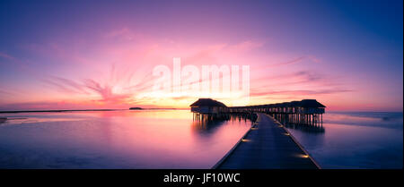 Amazing sunset beach in Maldives, with luxury over water villas and perfect sunset sky. Dreamy summer vacation and - Stock Photo