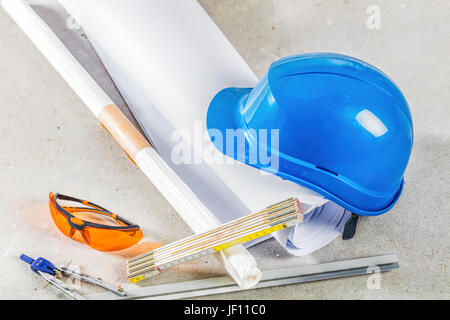 Hard hat, safety glasses and blueprints at the construction site. Building and engineereing tools close up. - Stock Photo