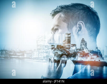 Young businessman thinking. Double exposure city downtown background. Smart business - Stock Photo
