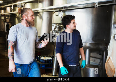 Two men working in a brewery, walking past large metal kettles, holding digital tablet. - Stock Photo