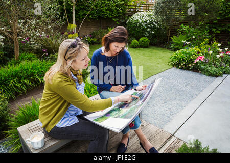 Two women sitting on a bench in a garden, looking at a portfolio with gardening images, discussing garden design. - Stock Photo
