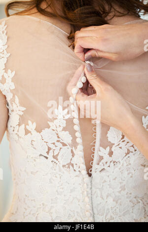 Hands doing up the small buttons on the back of a wedding dress with a net bodice and lace detail.  A bride getting - Stock Photo
