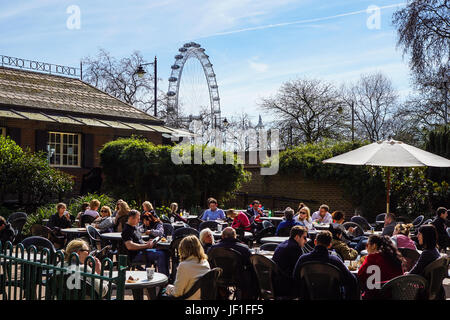 LONDON, ENGLAND, UK - APRIL 24 2017 : unidentified people relax in the park lunch break. Is widespread eating lunch - Stock Photo