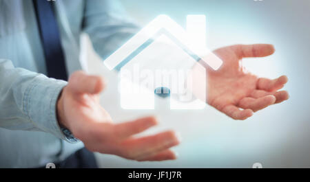 Businessman on blurred background holding 3D rendering icon house in his hand - Stock Photo