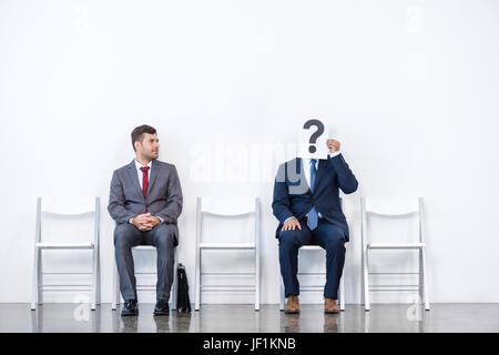 businessmen in suits sitting on chairs at white waiting room. business meeting - Stock Photo