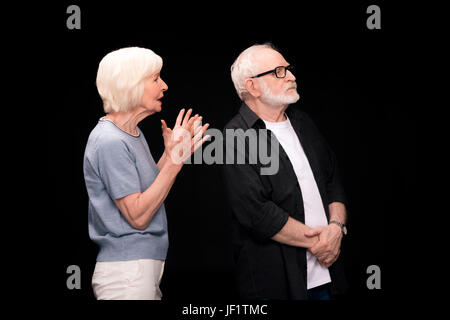 Serious senior couple standing and arguing isolated on black - Stock Photo