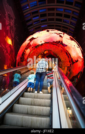 Family on Escalator passing through Planet Earth in the Natural History Museum London - Stock Photo