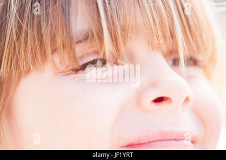 Extreme close up of a young girl's face. Beautiful child portrait. Female kid with blonde hair  pale white skin - Stock Photo