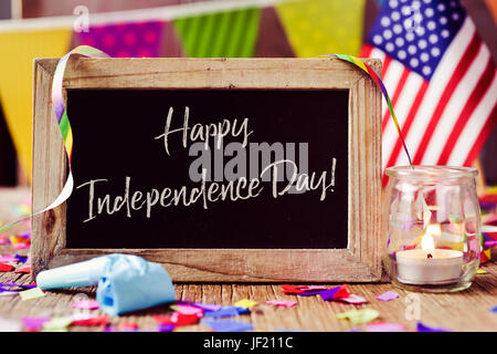 wooden-framed chalkboard with the text happy independence day written in it and an American flag, placed on a rustic - Stock Photo