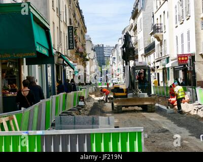 Construction activities, rue Daguerre, workers, heavy machinery, green safety fence, while pedestrians work to skirt - Stock Photo