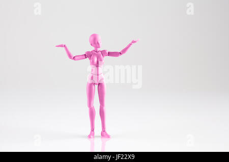 Pink female figurine standing isolated on reflective white background  with both hands up. Trying to make a decisioin - Stock Photo