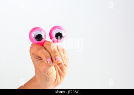 Funny character creature looking surprised and amused depicted with female hand and googly eyes. Isolated on white - Stock Photo