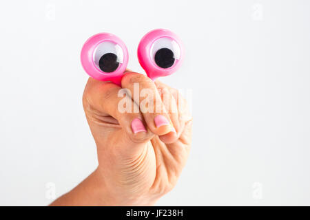 funny character creature looking surprised and puzzled depicted with female hand and googly eyes. Isolated on white - Stock Photo