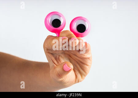 funny character creature looking surprised with open mouth, depicted with female hand and googly eyes. Isolated - Stock Photo