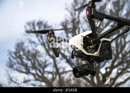 A DJI Inspire 1 Pro with a Zenmuse X5 Camera payload in flight. - Stock Photo