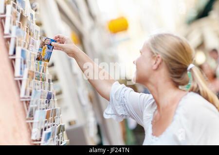 Smiling woman choosing postcards - Stock Photo