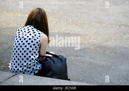 Teenager sitting on a staircase - Stock Photo