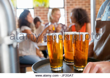 Close Up Of Pints Of Beer With Customers Drinking In Background - Stock Photo