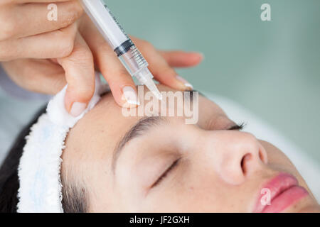 Doctor applying a facial treatment using a syringe - Stock Photo