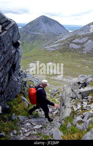 Lone Male Hill Walker Climbing down a Gully on the Western Ridge of the Scottish Mountain Graham Beinn Shiantaidh - Stock Photo