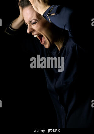 Сoming out into the light. angry woman in the dark dress isolated on black background - Stock Photo