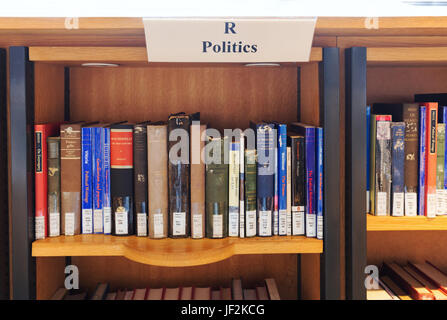 Politics books in a library on library shelves, England UK