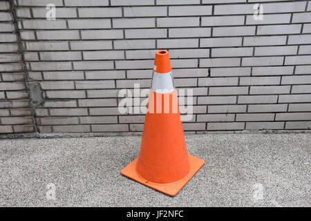 A single warning cone near a wall along a sidewalk kept there to reserve a parking place for a scooter. - Stock Photo