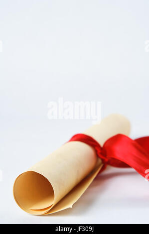 A rolled up parchment scroll, tied with a red ribbon to suggest graduation diploma or award. - Stock Photo
