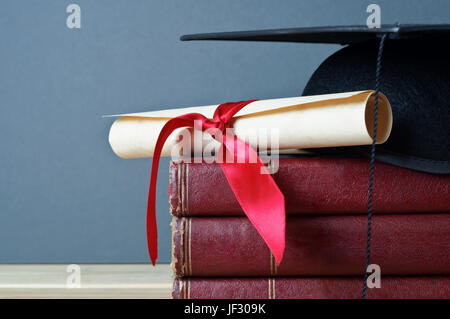 Close up of a mortarboard and graduation scroll on top of a pile of old, worn books, placed on a light wood table - Stock Photo