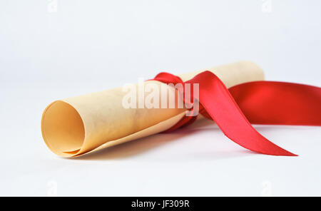 Close up of a rolled up diploma scroll, tied with a red ribbon. - Stock Photo