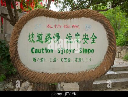 Bilingual sign warning of slippery slope in public park, Xuzhou, Jiangsu, China - Stock Photo