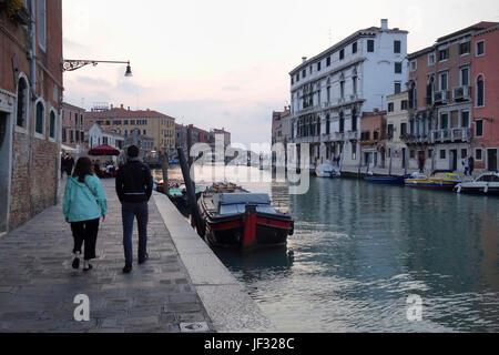 Pedestrians walking along a canal at dusk, Venice, Italy