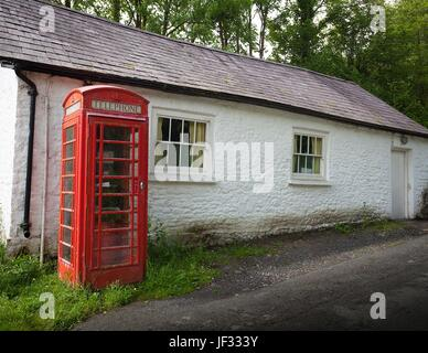 An old British phone box and a white washed building - Stock Photo