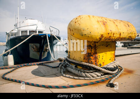 Old yellow bollard in the port - Stock Photo