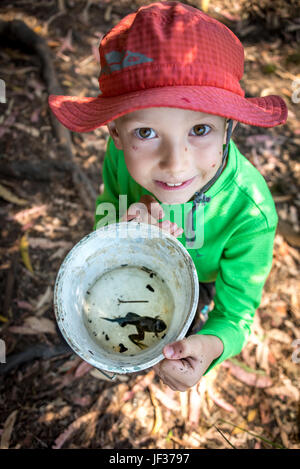 Hiking or camping with kids; a young boy looking up showing a big tadpole / pollywog / frog he found, the frog in bucket still has a tail.