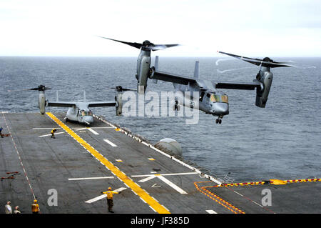 051115-N-3527B-068  A U.S. Marine Corps MV-22B Osprey executes a vertical take off from the flight deck of the amphibious assault ship USS Wasp (LHD 1) as another waits to launch during flight operations in the Atlantic Ocean on Nov. 15, 2005.  The Osprey is an advanced technology, vertical/short takeoff and landing multipurpose tactical aircraft and is scheduled to replace the aging CH-46E Sea Knight and CH-53D Sea Stallion helicopters currently in service.  These Ospreys are assigned to Marine Tiltrotor Operational Test and Evaluation Squadron 22 of Marine Corps Air Station New River, N.C.   Stock Photo